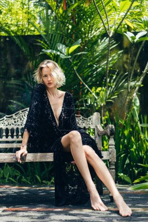 blond woman in black clothing with cigarette in hand resting on bench on terrace, ubud, bali, indonesia