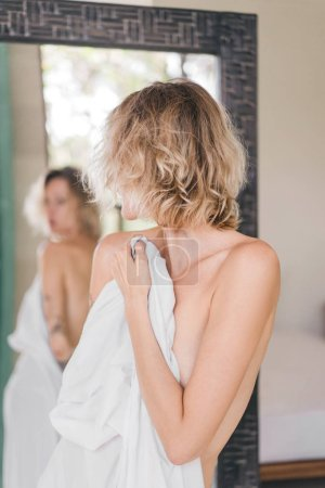 partial view of mirror reflection of blond woman covering body with white bedsheet