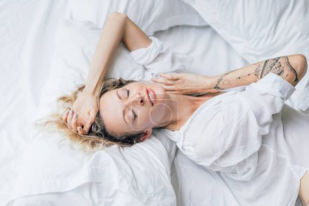 beautiful blond woman with eyes closed in white shirt resting on bed