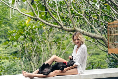 beautiful blond woman resting on terrace together with black dog, ubud, bali, indonesia