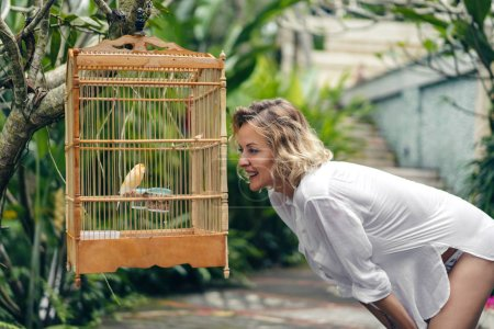 side view of smiling woman looking at bird in cage, ubud, bali, indonesia
