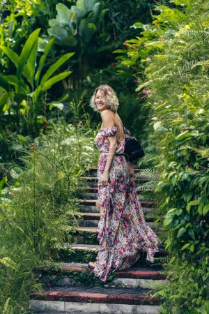 side view of smiling blond woman in dress standing on steps among green plants, ubud, bali, indonesia