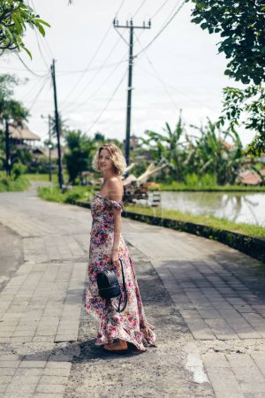 side view of attractive blond woman in dress standing on street, ubud, bali, indonesia