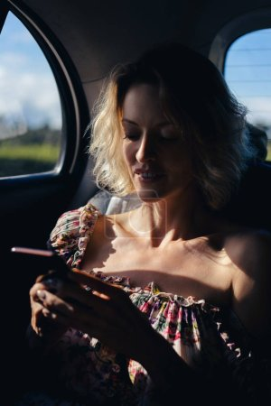 portrait of woman using smartphone in car