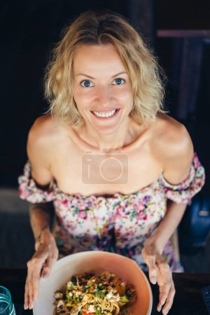 high angle view of cheerful blond woman sitting at table with dish and looking at camera