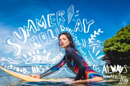 Photo for Sportswoman in wetsuit on surfing board in ocean at Nusa dua Beach, Bali, Indonesia. Lettering and drawing for Summer holiday - Royalty Free Image