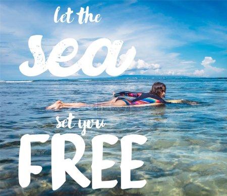 Photo pour Vue de côté de jeune sportive en combinaison sur planche de surf dans l'océan à la plage de Nusa dua, Bali, Indonésie. Inspiration - laissez la mer vous affranchira - image libre de droit