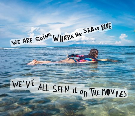 Photo for Young sportswoman in wetsuit on surfing board in ocean at Nusa dua Beach, Bali, Indonesia. Lettering - We are going where the sea is blue, Weve all seen it on the movies - Royalty Free Image