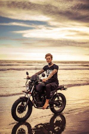 Photo pour Beau tatoué motard moto sur la plage de l'océan et en regardant la caméra - image libre de droit