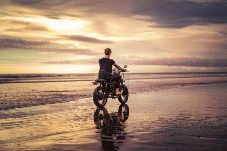 back view of tattooed biker riding motorbike on ocean beach