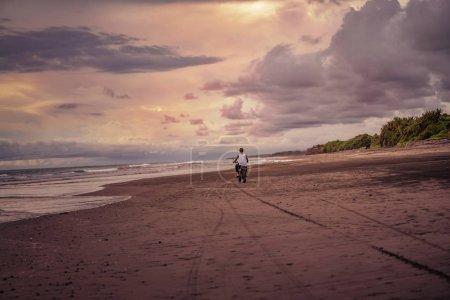 Photo pour Vue arrière du homme moto sur la plage de l'océan - image libre de droit