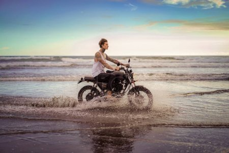 side view of handsome tattooed man riding motorcycle in ocean waves on beach