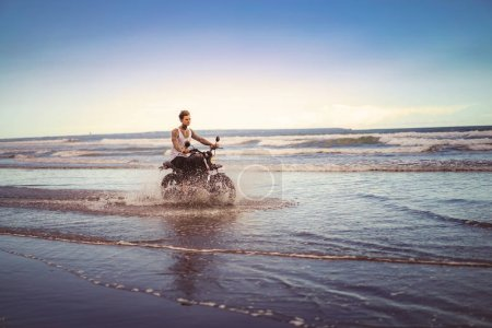 Photo for Handsome tattooed biker riding motorcycle in ocean waves on beach - Royalty Free Image
