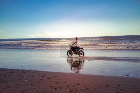 tattooed man riding motorcycle on ocean beach during sunrise