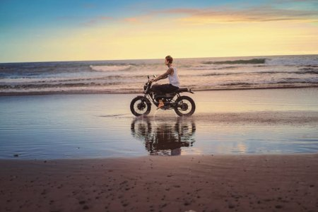 side view of tattooed biker riding motorcycle on ocean beach during sunrise