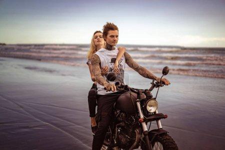 Photo pour Jeune élégant tatoué moto CIRC. couple sur la plage de l'océan - image libre de droit