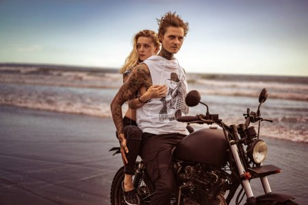 Photo for Attractive girlfriend hugging boyfriend from back on motorcycle on ocean beach - Royalty Free Image