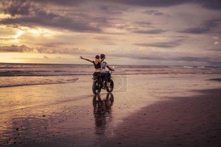 Photo pour Vue arrière du couple moto sur la plage de sable de l'océan - image libre de droit