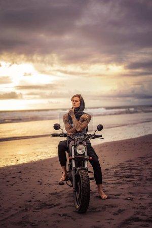pensive handsome tattooed biker sitting on motorcycle on ocean beach