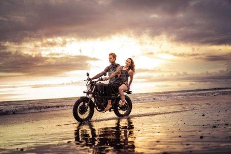 Photo pour Moto sur la plage de l'océan avec beau lever de soleil sur fond de couple - image libre de droit