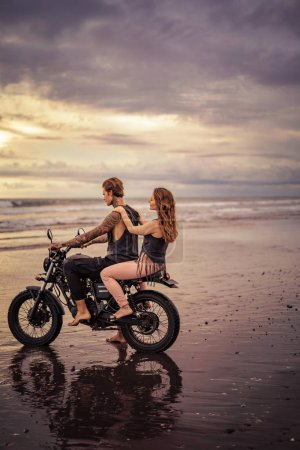 side view of couple sitting on motorcycle at beach during sunrise