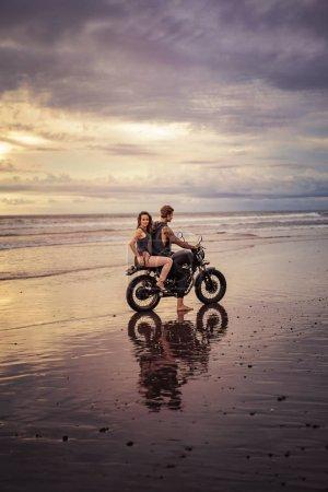 Photo pour Copain et copine assis sur la moto sur la plage pendant le lever du soleil et le temps nuageux - image libre de droit