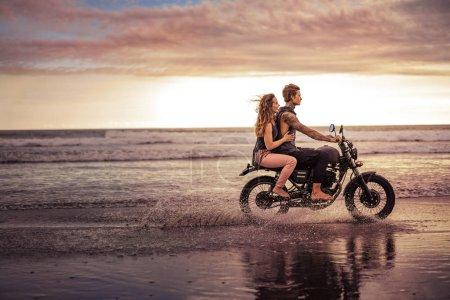 Photo pour Vue latérale du couple moto sur la plage de l'océan - image libre de droit