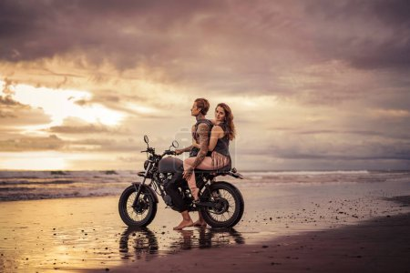 girlfriend hugging boyfriend and they sitting on motorcycle at beach during sunrise