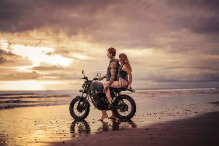 boyfriend and girlfriend hugging on motorcycle at beach during sunrise