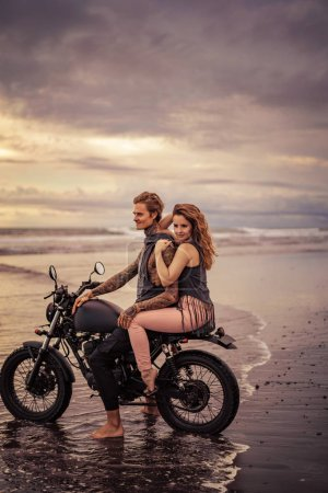Photo for Attractive girlfriend and boyfriend sitting on motorcycle at beach during sunrise - Royalty Free Image