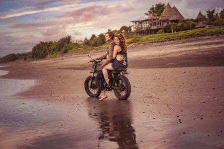 boyfriend and girlfriend sitting on motorcycle at beach during sunrise