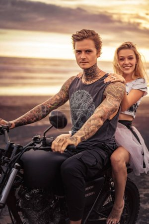 Photo for Young heterosexual couple sitting on motorcycle and looking at camera at beach - Royalty Free Image