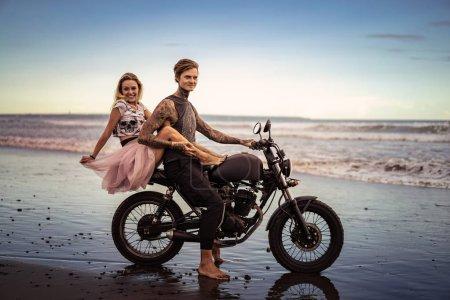 Photo pour Couple souriant étreindre sur la moto sur la plage de l'océan pendant beau lever de soleil - image libre de droit