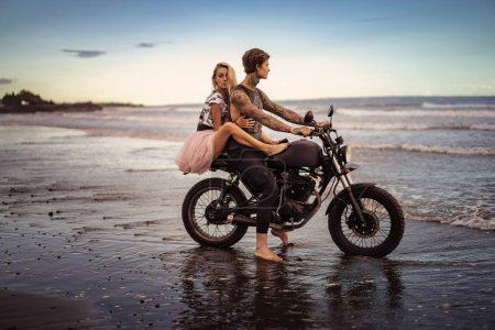 Photo for Side view of couple hugging on motorcycle on ocean beach - Royalty Free Image