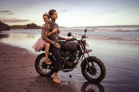 smiling girlfriend hugging boyfriend on motorcycle on ocean beach