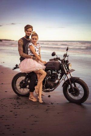 Foto de Pareja abrazándose en motocicleta en la playa del océano durante el hermoso amanecer y mirando a cámara - Imagen libre de derechos