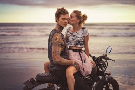 Photo for Girlfriend kissing boyfriend on motorcycle on ocean beach during beautiful sunrise - Royalty Free Image