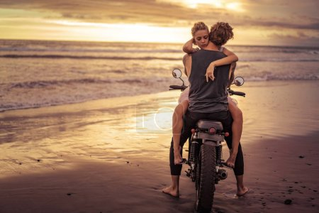 Photo for Heterosexual couple hugging on motorcycle on ocean beach during beautiful sunrise - Royalty Free Image