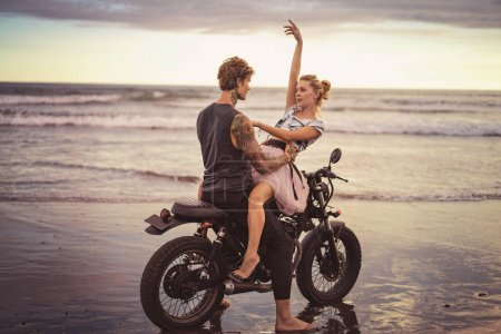 young couple hugging on motorcycle on ocean beach during beautiful sunrise