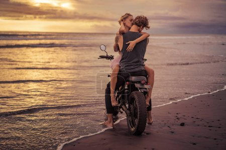 Photo for Couple hugging on motorcycle on ocean beach during beautiful sunrise - Royalty Free Image