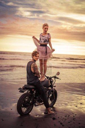 happy girlfriend standing on motorcycle near boyfriend on ocean beach