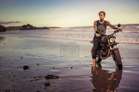 tattooed man sitting on motorbike on ocean beach and looking away