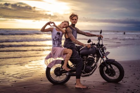 girlfriend leaning on boyfriend on motorcycle and showing heart with fingers on ocean beach