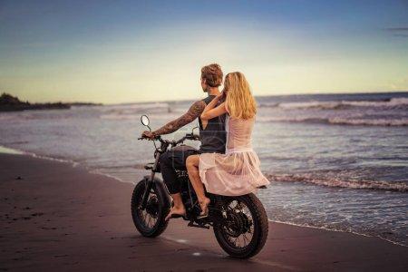 back view of boyfriend and girlfriend riding motorbike on ocean beach during sunrise