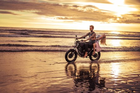 affectionate boyfriend and girlfriend riding motorcycle on ocean beach during sunrise