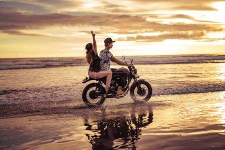 Photo pour Vue latérale du couple moto ensemble sur la plage de l'océan pendant le lever du soleil - image libre de droit