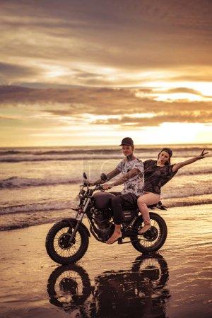 Photo pour Heureux couple moto au bord de mer pendant le lever du soleil - image libre de droit