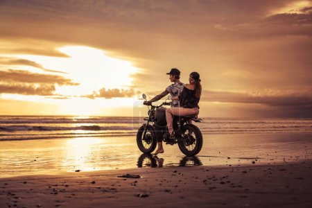 affectionate couple sitting on motorcycle on ocean beach during sunrise
