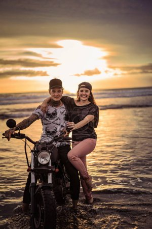 smiling couple with motorcycle on ocean beach