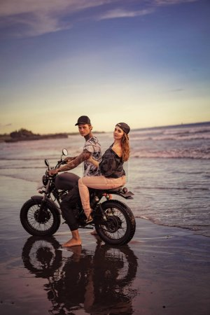 Photo for Side view of couple riding motorcycle on seashore - Royalty Free Image